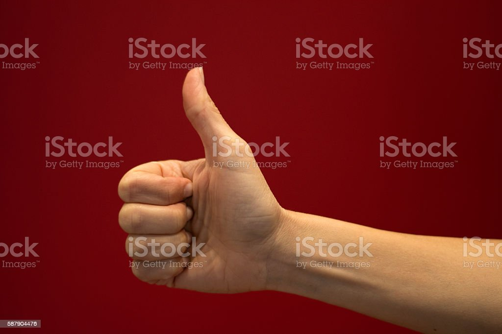 Thumb up sign with hand stock photo