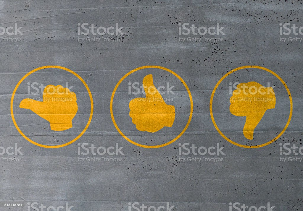 thumb valuation icons on cement concept stock photo