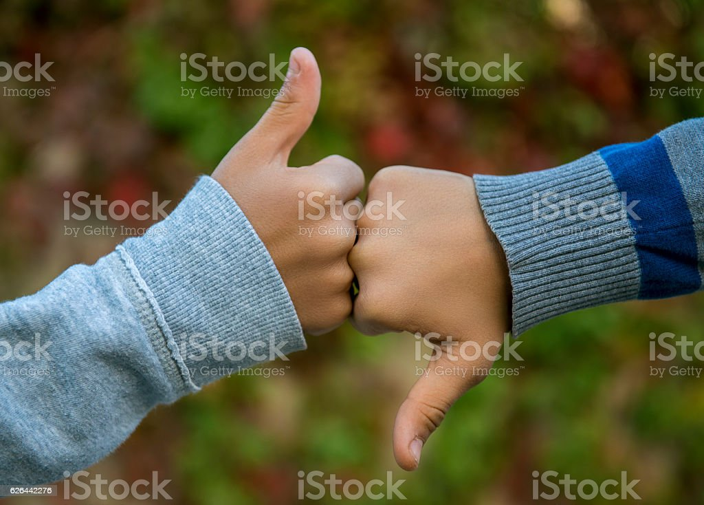 Two people gesturing thumbs up and thumbs down in same time....