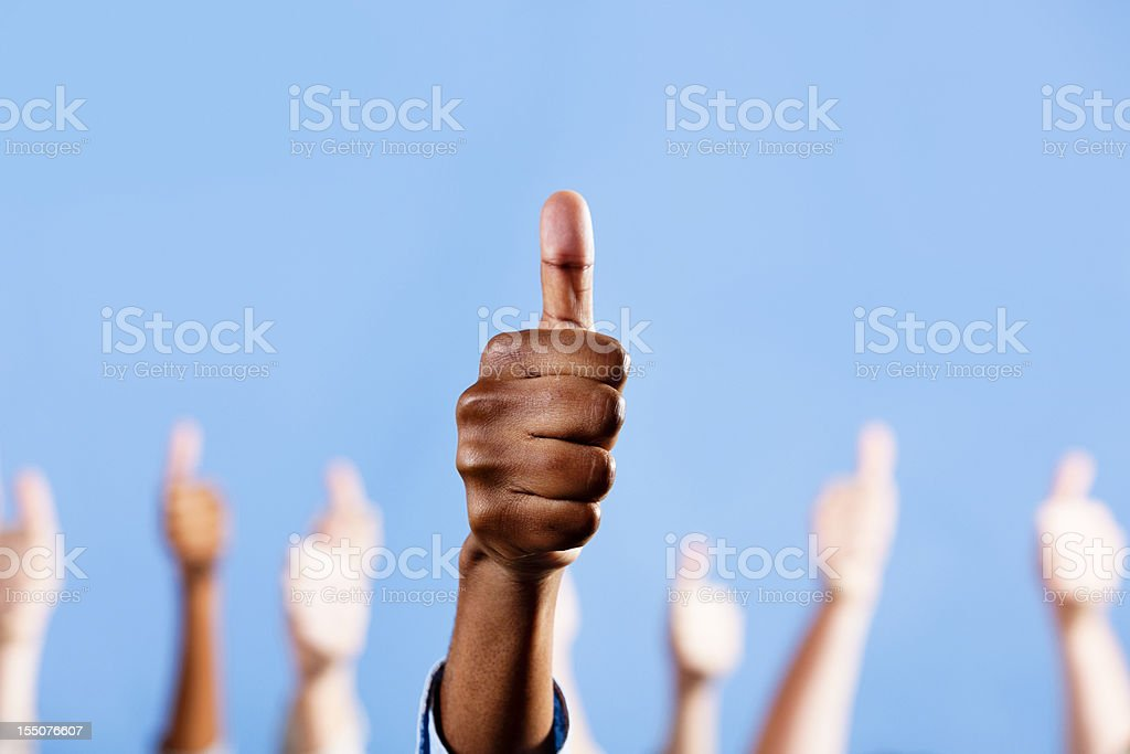Thumbs up! Male African-American hand gestures, others in background royalty-free stock photo