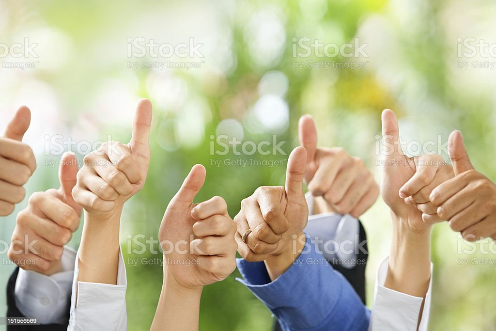 Thumbs up on green background stock photo