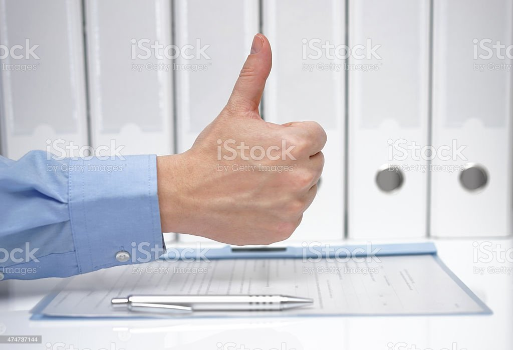 thumbs up over signed contract and binders stock photo