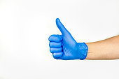Thumbs up. Profile view of hand in blue medical glove.