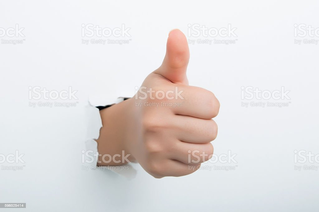 Thumbs up through the paper hole isolated on white background stock photo