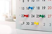 thumbtacks in calendar - concept of busy schedule