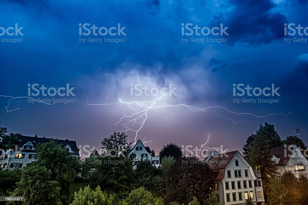 thunderstorm and thunderbolt over houses in Switzerland stock photo