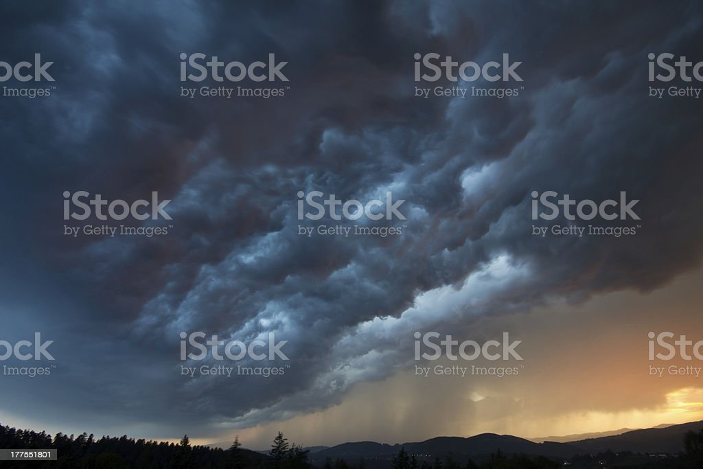 A thunderstorm rolled in as the sun set on the horizon stock photo