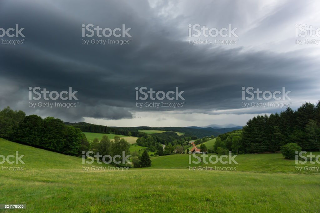 Thunderstorm with rain coming to green meadows in black forest