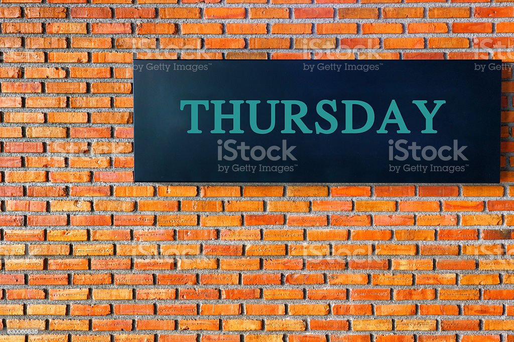 Thursday letters on a black background with  brick wall stock photo