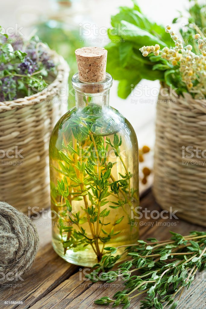 Thyme essential oil or infusion and basket of healing herbs. stock photo