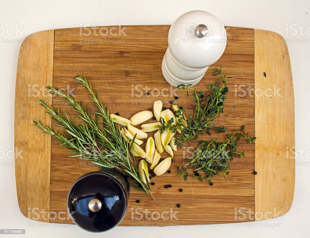Thyme, rosemary, garlic, salt, pepper on the wooden cutting board stock photo