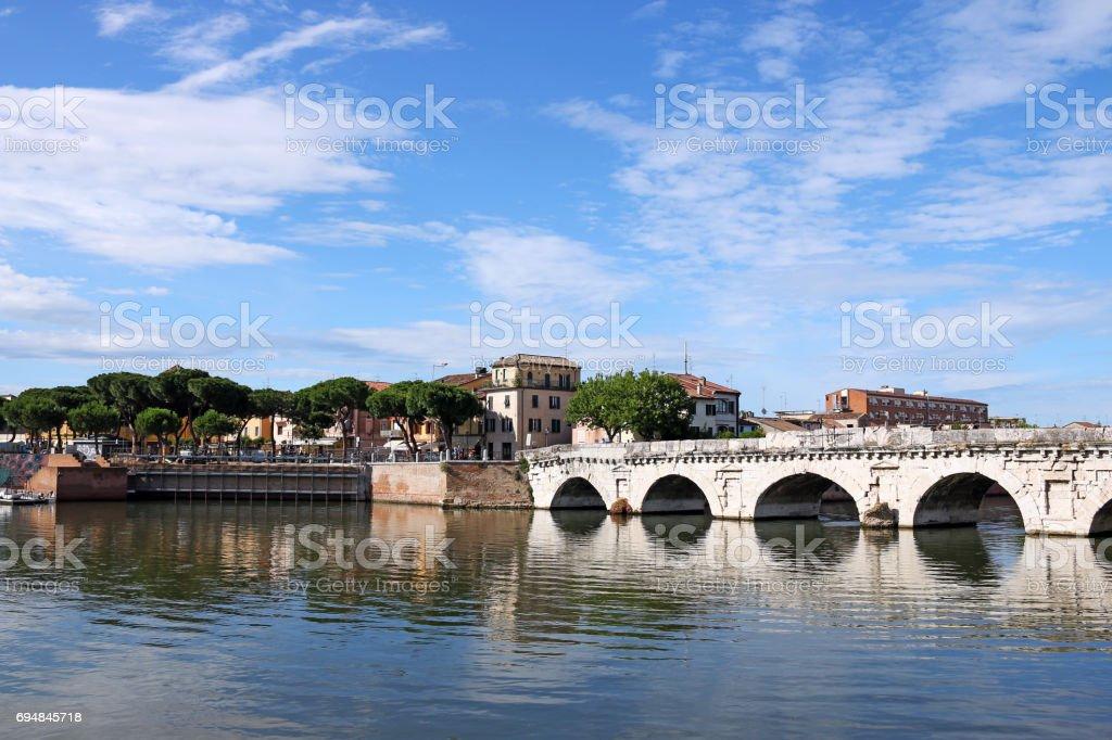 Tiberius bridge and buildings Rimini Italy stock photo