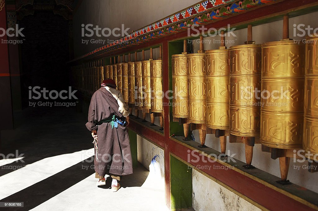 Tibet Old Woman and Prayer Wheels royalty-free stock photo