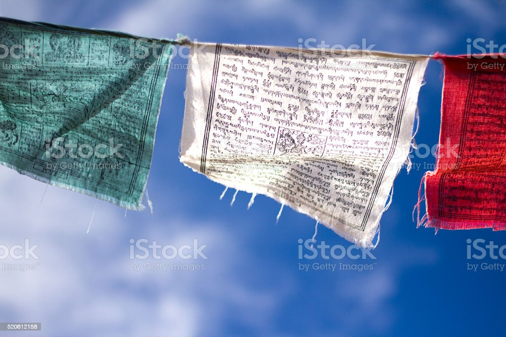 Tibetan Buddhist Prayer Flags Against Cloudy Blue Sky (Close-Up) stock photo