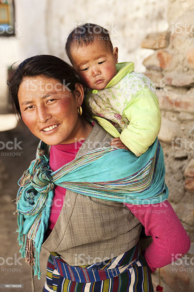 Tibetan child carried on mother's back stock photo
