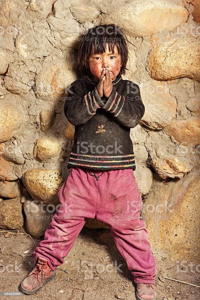 Tibetan child standing in front of the house. Mustang, Nepal. stock photo