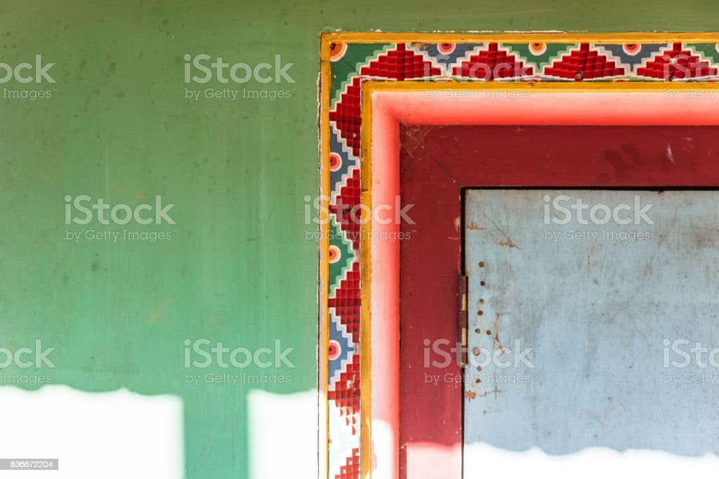 Tibetan decoration wall with green, red and yellow color with sunlight of Guru Rinpoche Temple at Namchi. Sikkim, India. stock photo