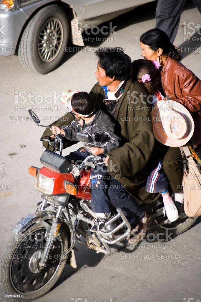 Tibetan Family Driving on a Motorbike royalty-free stock photo