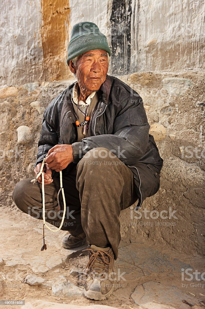 Tibetan man praying with rosary, near Lo Manthang stock photo