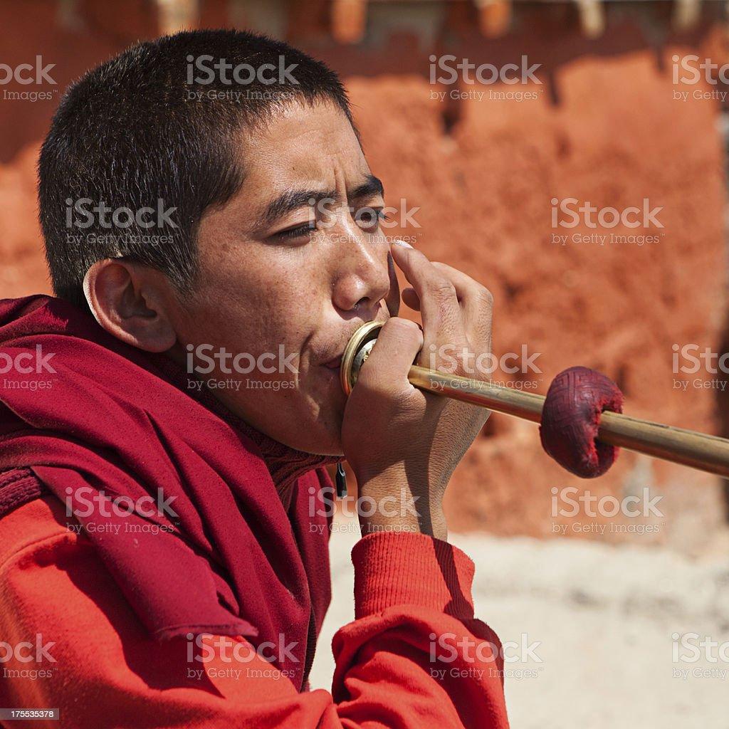 Tibetan monk playing buddhist horns royalty-free stock photo
