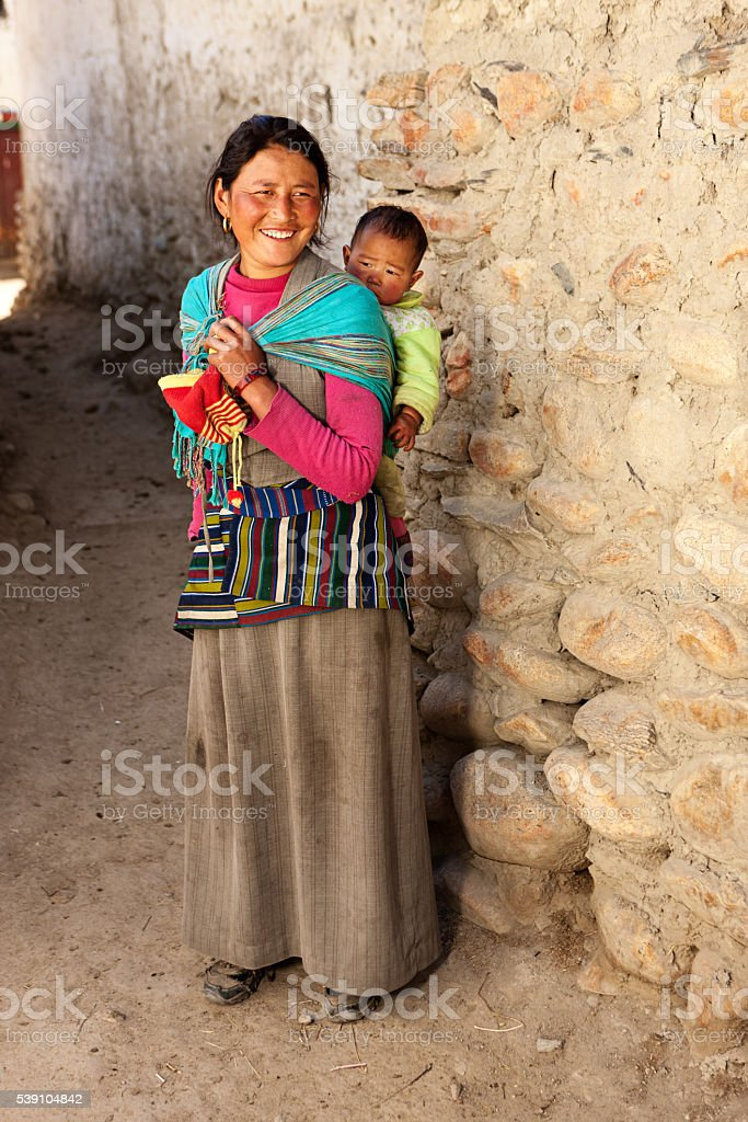 Tibetan mother carrying her baby, Upper Mustang stock photo