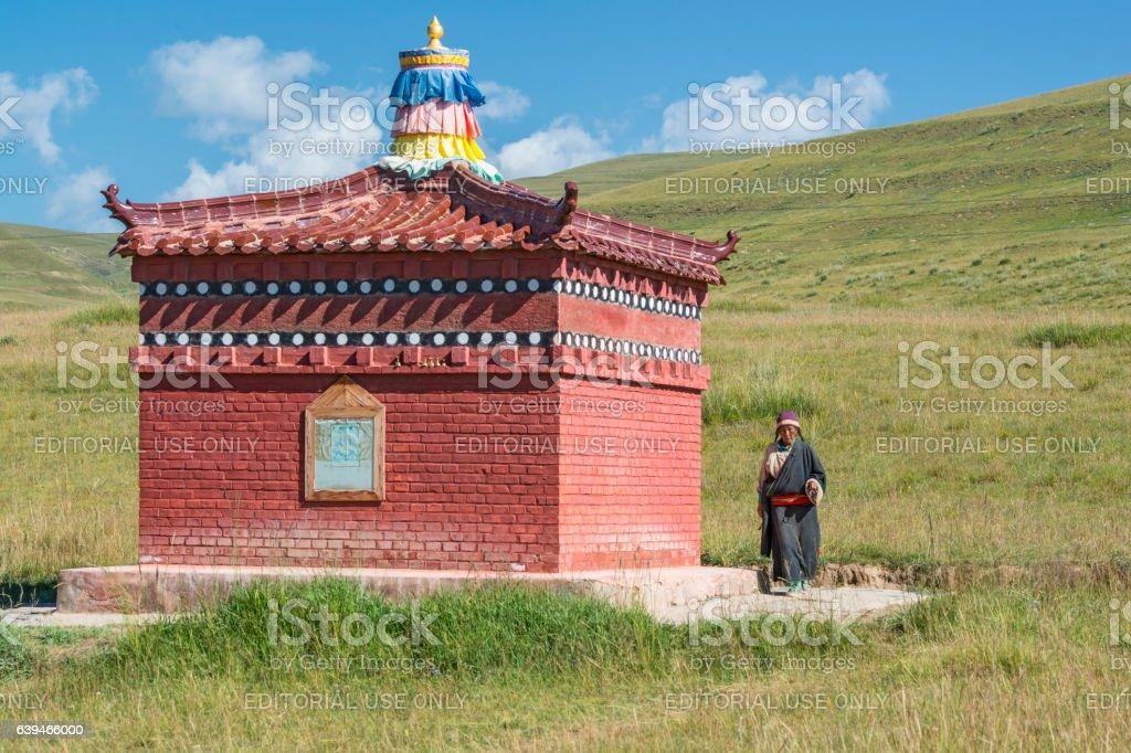 Tibetan pilgrim praying during her circumabulation, Amdo, Tibet stock photo