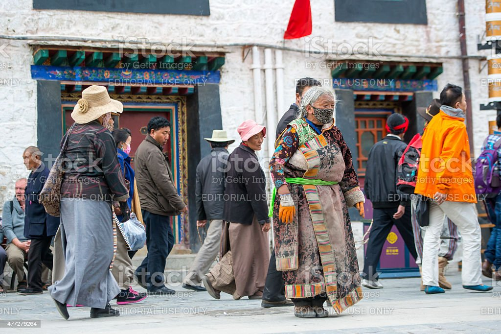 Tibetan pilgrim prostrating at the Barkhor in Lhasa, Tibet. stock photo