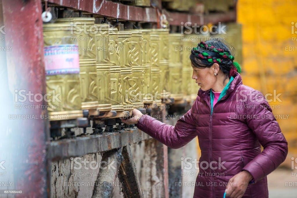 Tibetan pilgrim turning prayer wheels at Barkhor, Lhasa, Tibet stock photo