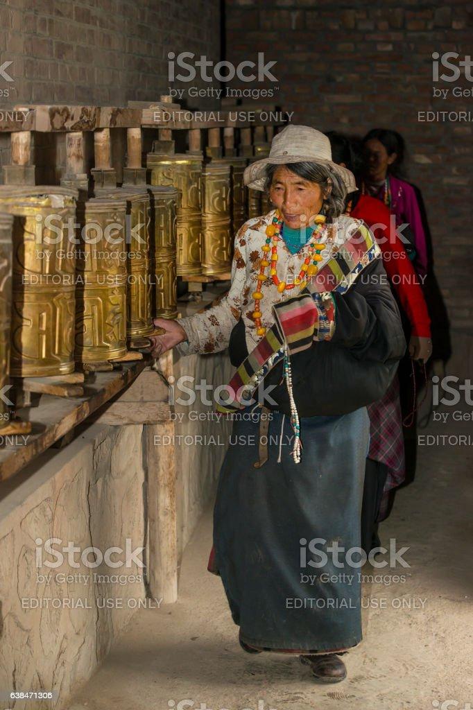 Tibetan pilgrims are turning prayer wheels stock photo