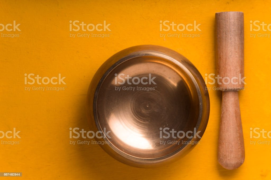 Tibetan singing bowl  on the yellow background top view stock photo