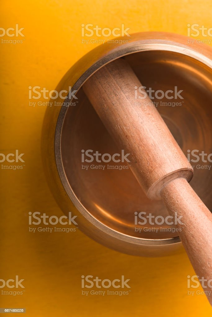 Tibetan singing bowl  on the yellow background vertical stock photo