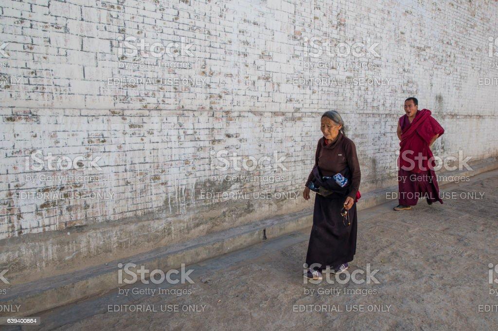 Tibetan woman and monk in Langmusi monastery, Tibet stock photo