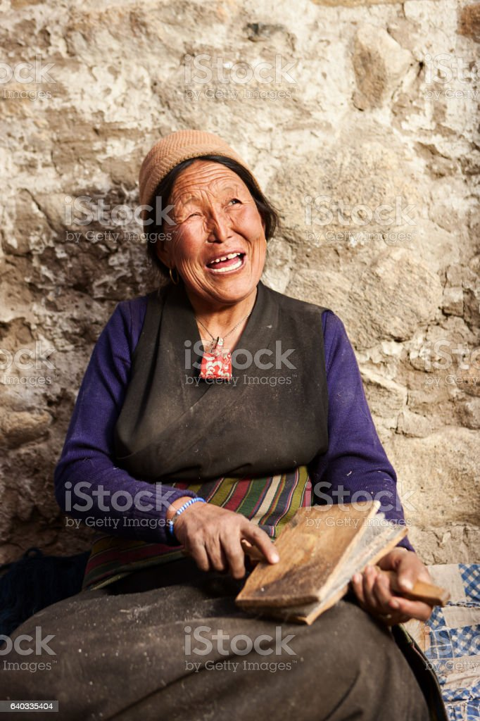 Tibetan woman combing wool in Upper Mustang stock photo