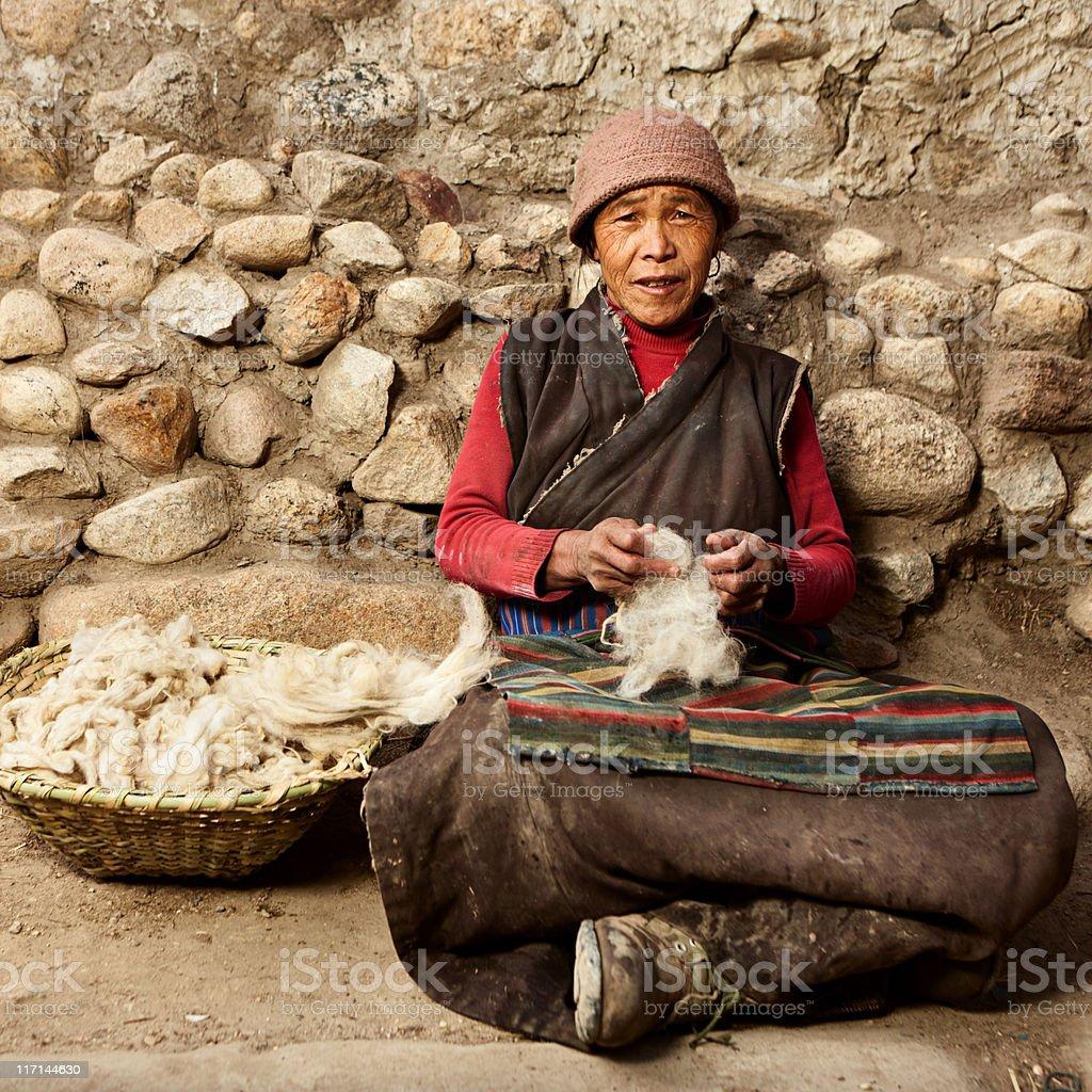 Tibetan woman combing wool royalty-free stock photo