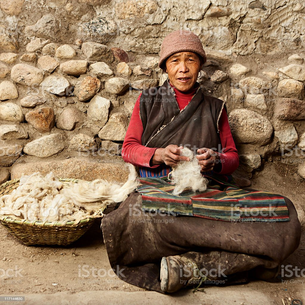 Tibetan woman combing wool stock photo
