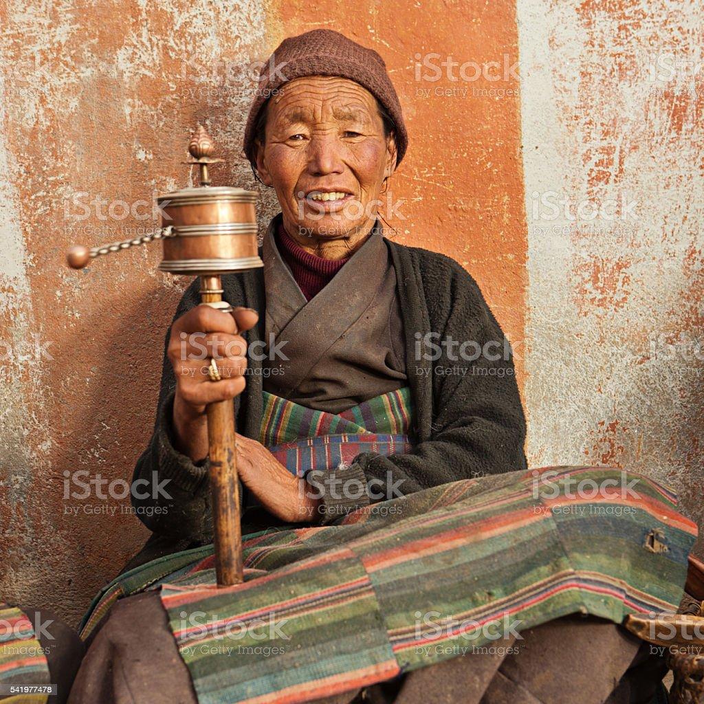 Tibetan woman holding praying wheel in Upper Mustang, Nepal stock photo