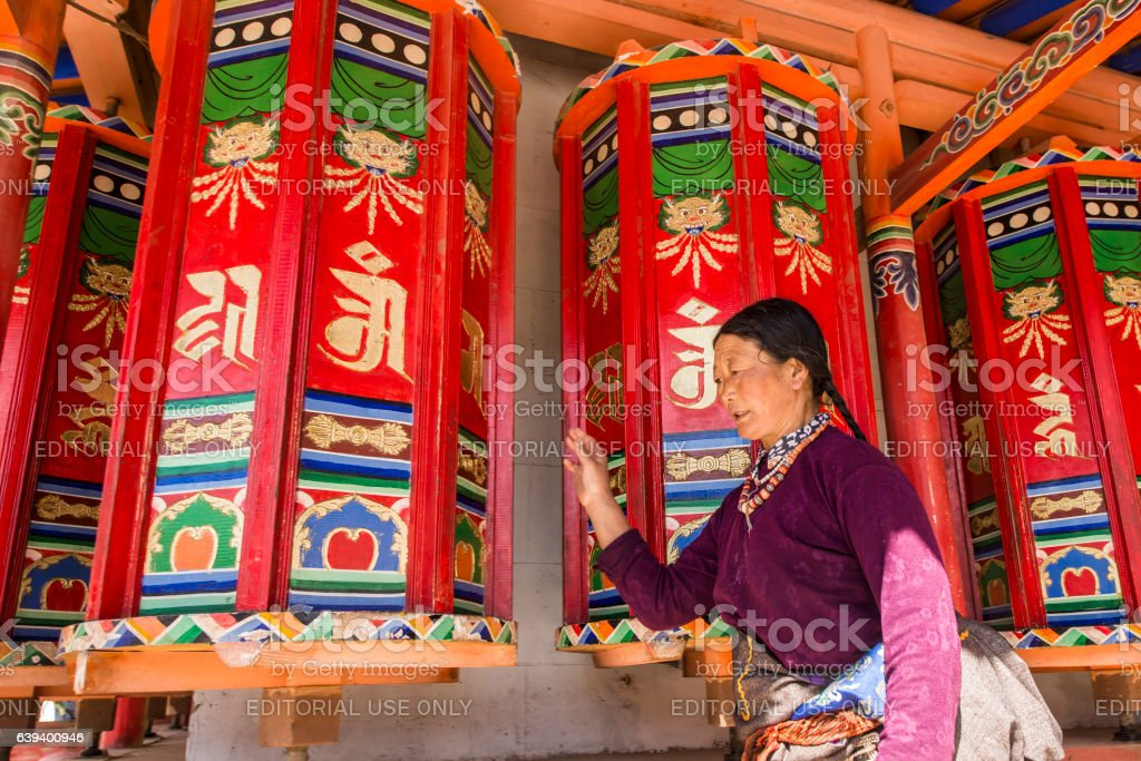 Tibetan woman is turning colorful prayer wheels, Langmusi monastery stock photo