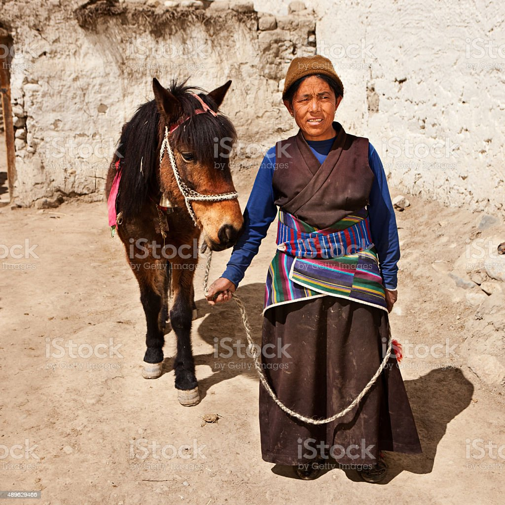 Tibetan woman leads her horse in Upper Mustang stock photo