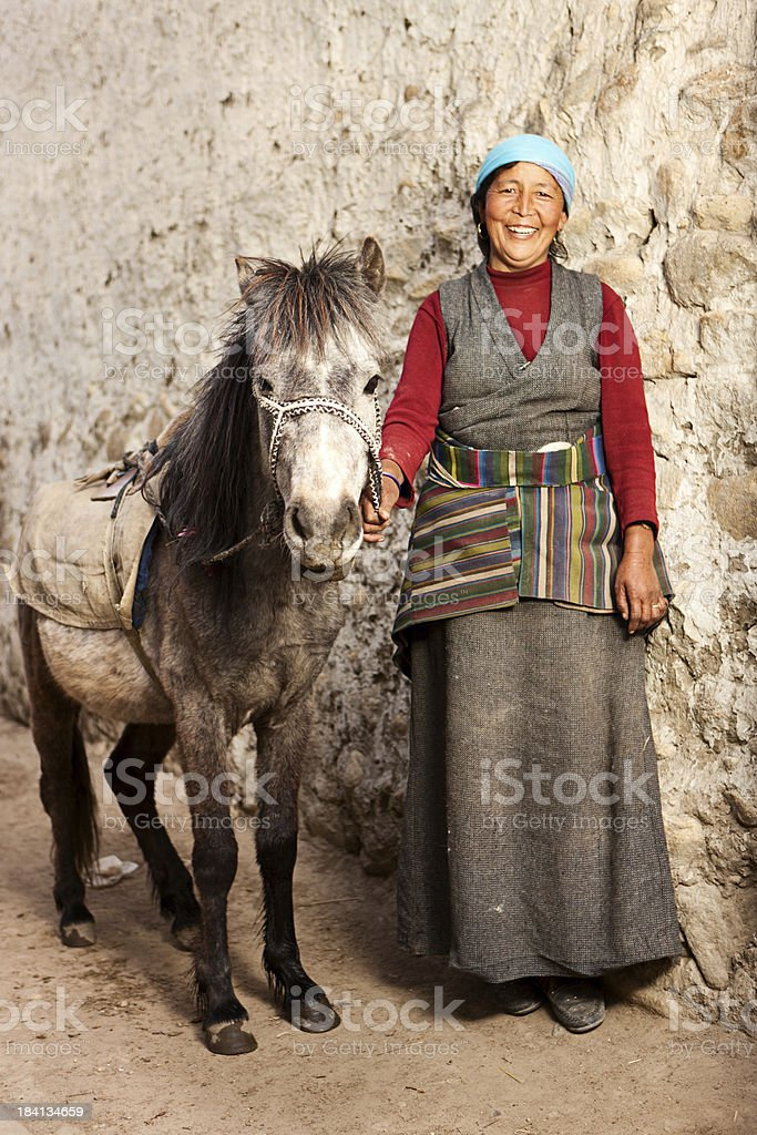 Tibetan woman leads her horse stock photo