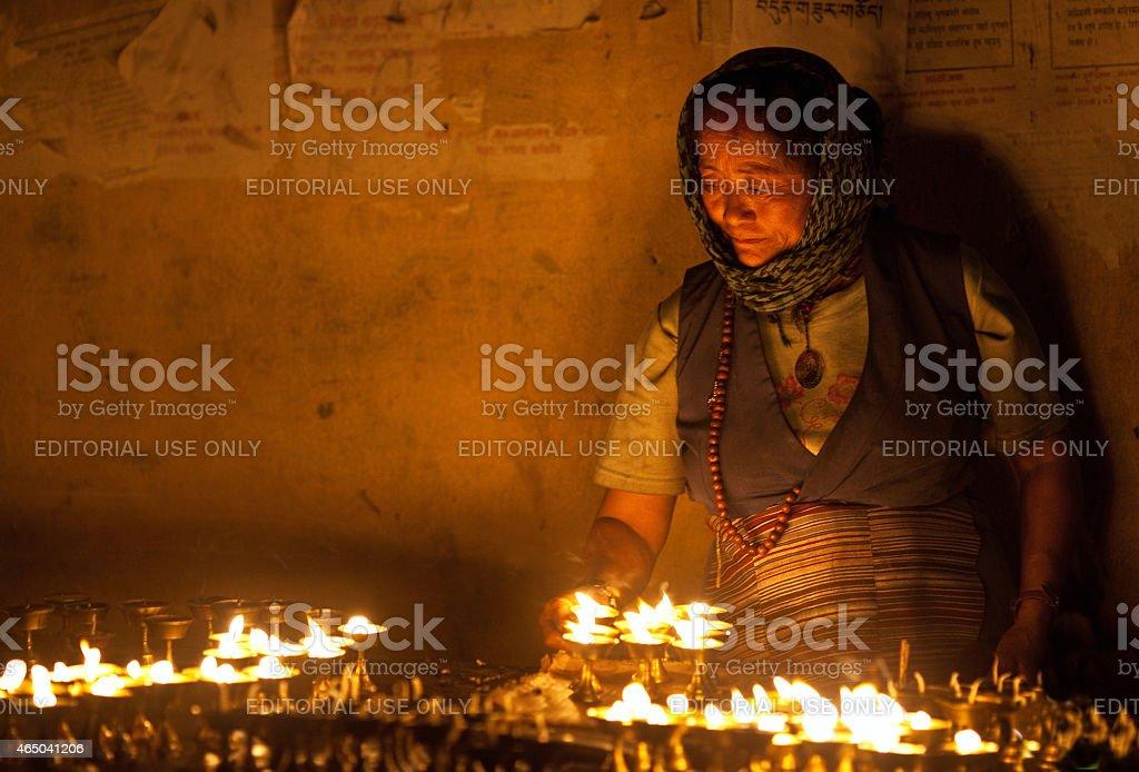 Tibetan woman lights incense butter candles stock photo