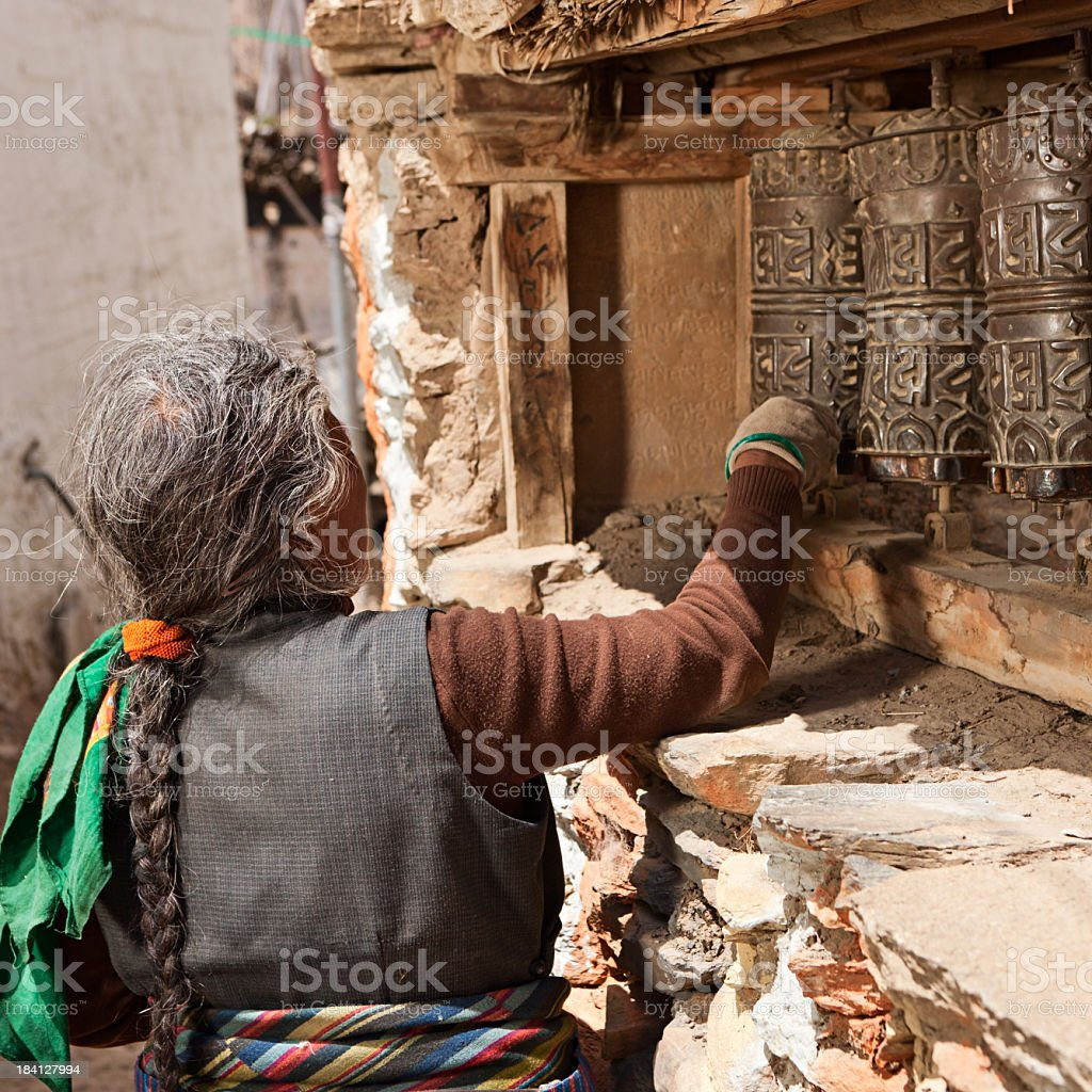 Tibetan woman spinning a prayer wheel. Mustang, Nepal royalty-free stock photo