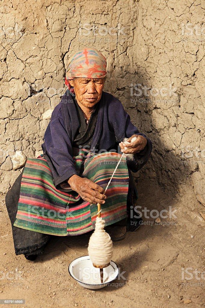 Tibetan woman spinning the wool. Mustang, Nepal stock photo