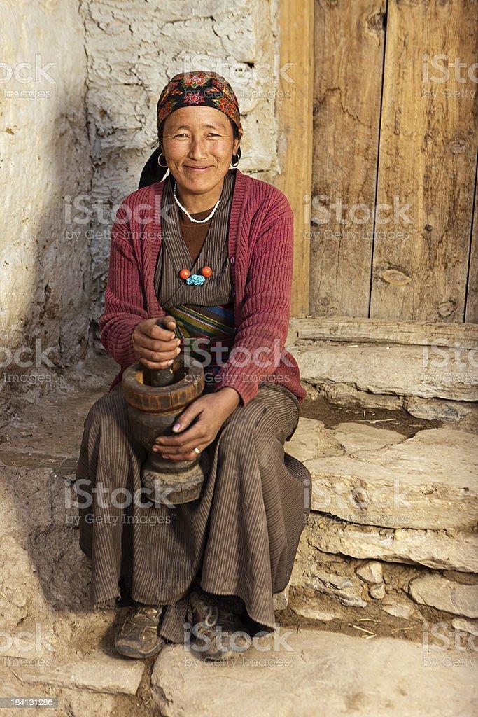 Tibetan woman using a mortar to make  flour. Mustang, Nepal royalty-free stock photo