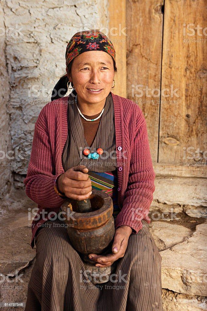 Tibetan woman using a mortar to make  flour. Mustang, Nepal stock photo