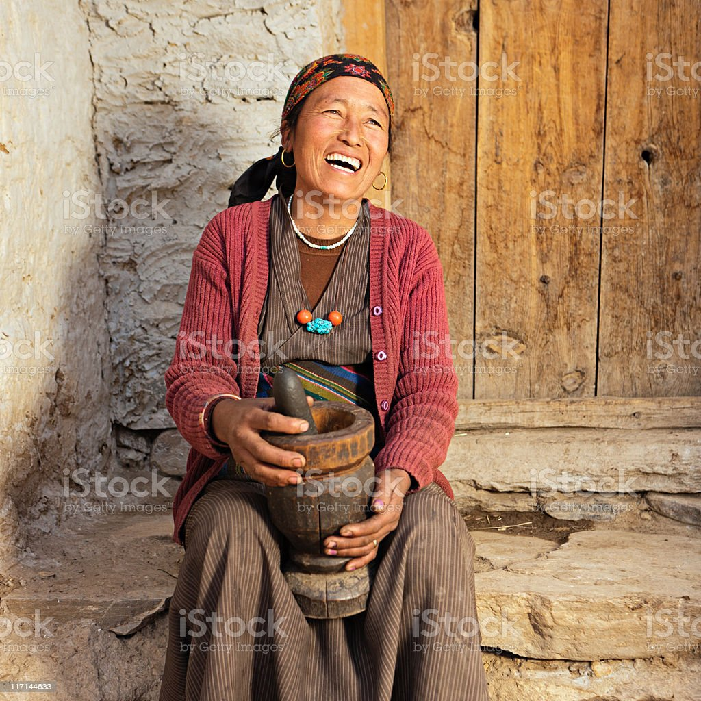 Tibetan woman using mortar stock photo