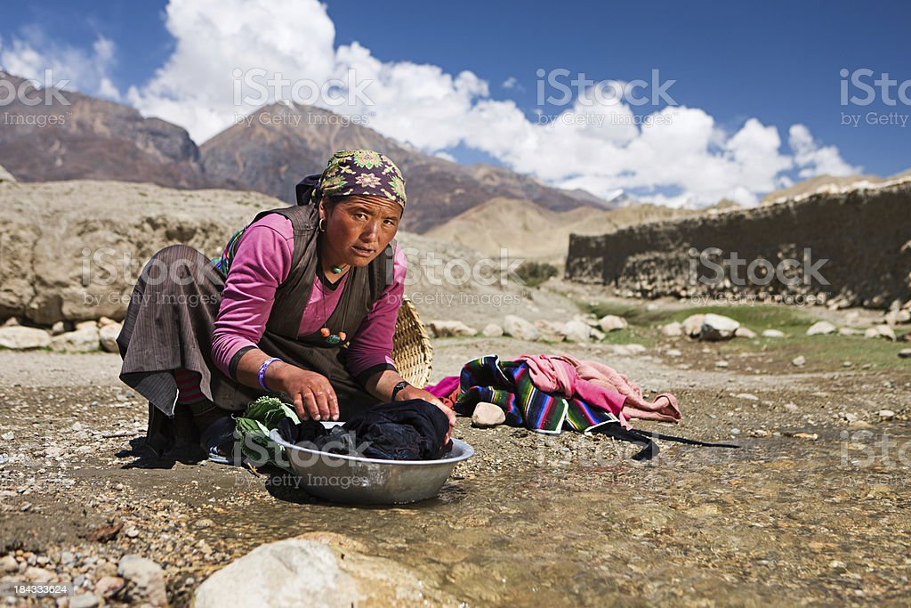 Tibetan woman washing clothes in the river. Mustang. royalty-free stock photo