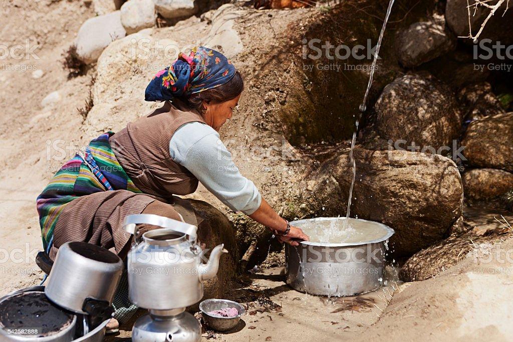 Tibetan woman washing dishes. Mustang, Nepal stock photo