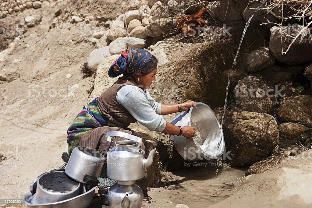Tibetan woman washing dishes. Mustang royalty-free stock photo