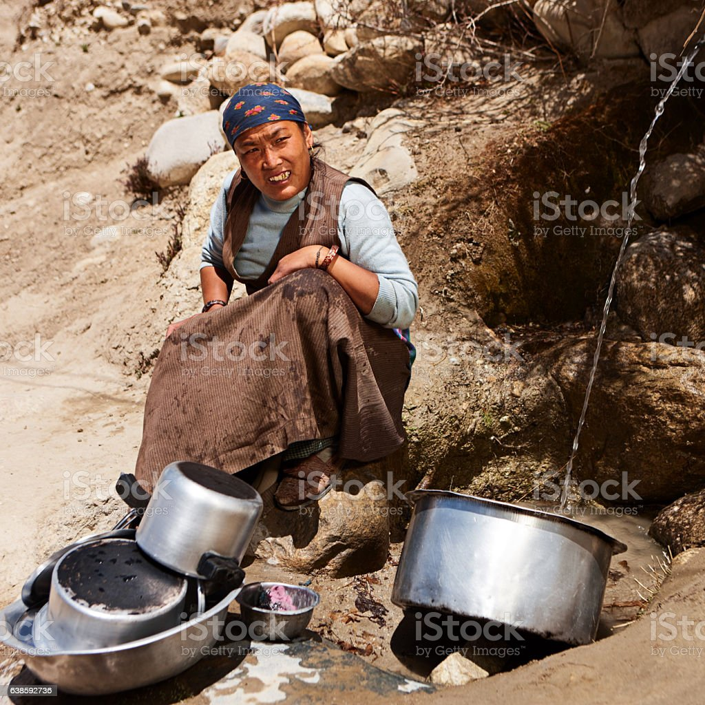 Tibetan woman washing dishes. Mustang stock photo