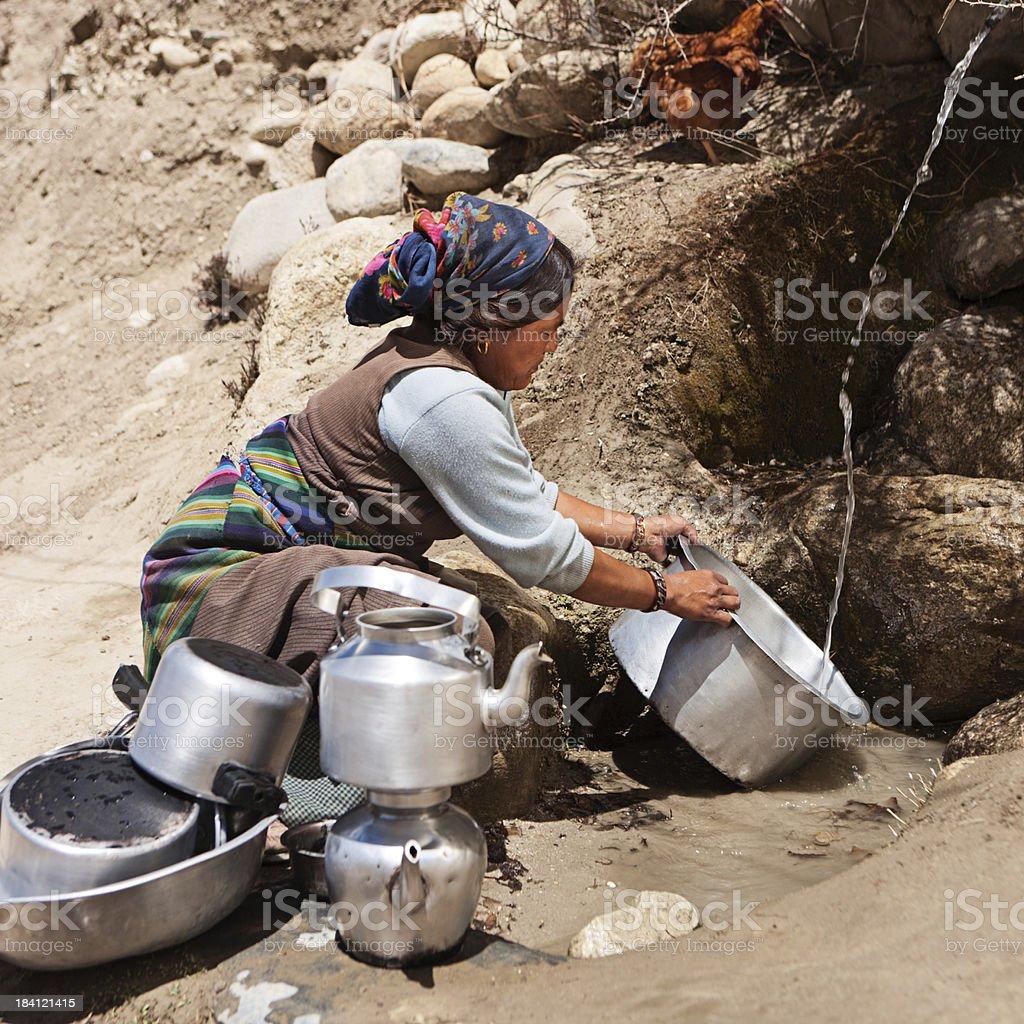 Tibetan woman washing dishes royalty-free stock photo